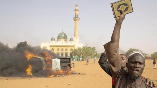 Un uomo alza un Corano durante una protesta in Niger contro il presidente Issoufou per la sua partecipazione al corteo anti-terrorismo di Parigi