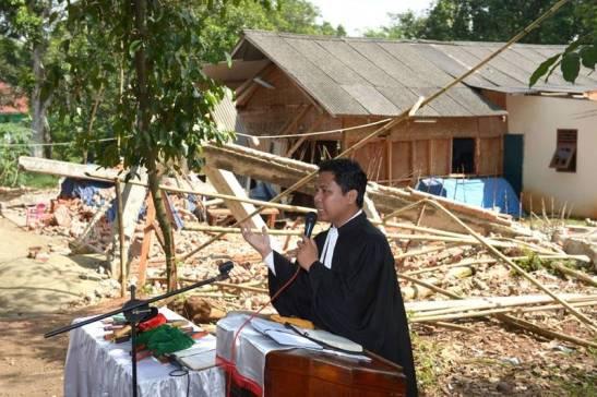 Un pastore indonesiano celebra la messa accanto a una chiesa distrutta