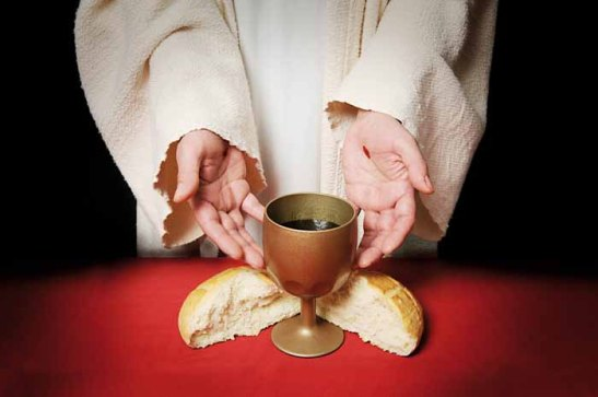 The hands of Jesus offering the Communion wine and bread