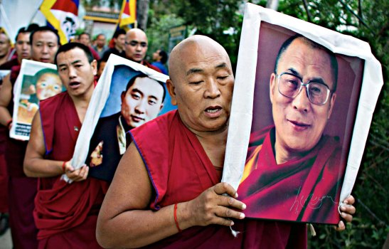An exiled Tibetan Buddhist monk carries a portrait of spiritual leader the Dalai Lama during a candlelit protest gathering in Dharmsala, India, Thursday, April 25, 2013. Reports say three Tibetans have died after setting themselves on fire to protest Chinese rule in a western region where authorities have imposed a heavy security presence. More than 100 Tibetans have self-immolated since 2011 to protest Chinese policies in the region and call for the return of their spiritual leader, the Dalai Lama, from exile. (AP Photo/ Ashwini Bhatia)