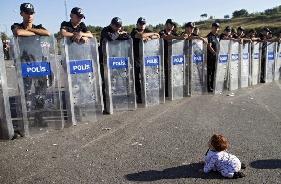 epa04937948 A Syrian refugee baby plays in front of riot police at the Istanbul-Edirne highway as they wait for permission to pass Turkish Greek border to reach Germany in Edirne, Turkey 19 September 2015. Turkey has spent 7.6 billion US dollar on caring for 2.2 million Syrian refugees since the civil war began in 2011, Deputy Prime Minister Numan Kurtulmus said on 18 September. Turkey hosts more Syrians who fled their homeland than any other country. Most Syrians, however, have no legal right to work and rights groups report housing remains a huge issue for many.  EPA/TOLGA BOZOGLU  EPA/TOLGA BOZOGLU