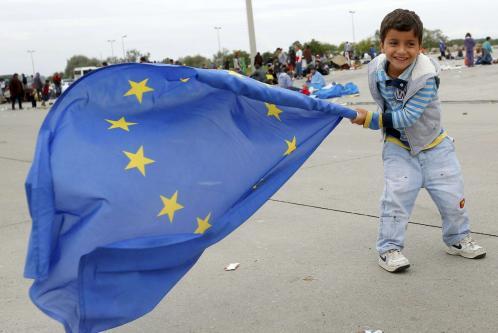 bimbo arrivato in Austria sventola felice la bandiera europea (LaPresse)