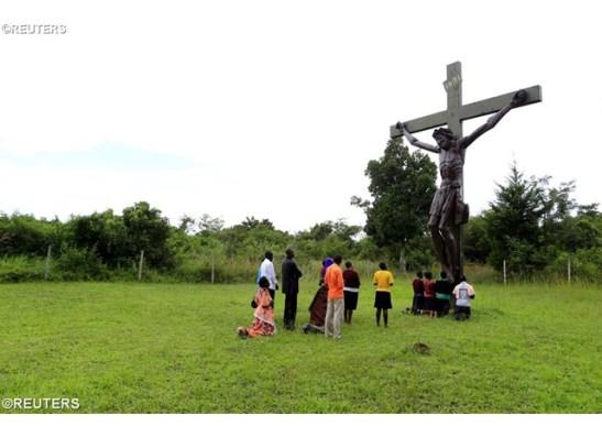 Fedeli ugandesi in preghiera vicino una croce nei pressi di Kampala