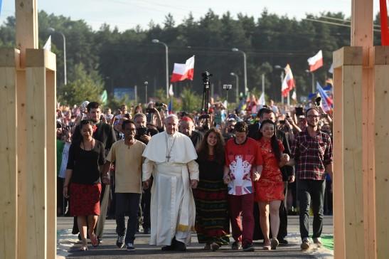 Le pape François, accompagné de jeunes du monde entier, passe la reproduction de la Porte de la Miséricorde au Campus Misericordiae lors des JMJ à Cracovie, le 30 juillet.jpg