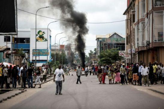 1089430-des-kinois-regardent-des-manifestants-bruler-des-pneus-au-cours-d-une-marche-anti-kabila-a-kinshasa-
