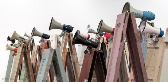 Kader Attia, Asesinos! Asesinos! installazione di 134 porte in legno, 47 megafoni, 2014.