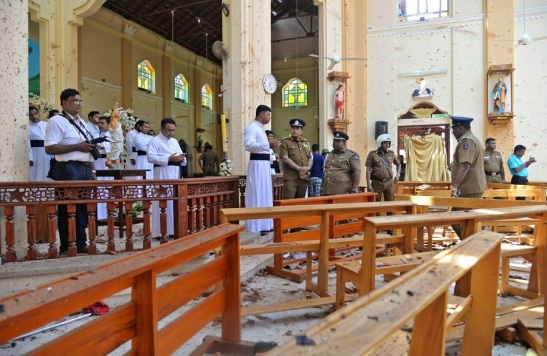 Clergy and police view the bomb damage at St Sebastian's in Negombo, Sri Lanka (CNS)