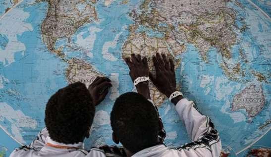 Giovani indicano l'Africa davanti un planisfero