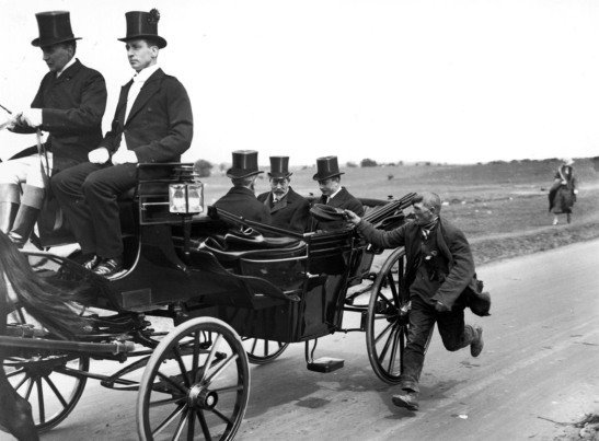 King George V. Photograph, taken in the early 1920's showing a beggar solicing money form the royal party as he runs alongside their carriage.