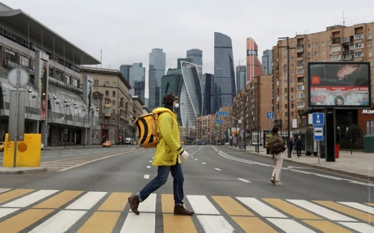 A Yandex.Eats food delivery courier crosses a street in Moscow